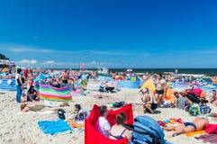 En sikt av en fullsatt strand med folk som kopplar av och badar royaltyfria foton