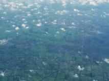 En sikt av moln och fält från ett flygplan royaltyfria foton