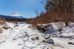 En sikt av Mont Fuji på en klar vinterdag från en liten ström, i Saiko sjöområde som täckas av ursprungligt insnöat de fem sjöarn arkivfoto
