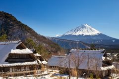En sikt av Mont Fuji på en klar vinterdag, från Saiko Iyashino-Sato Nenba den traditionella byn som täckas av ursprungligt insnöa arkivbilder