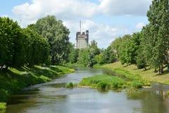 En sikt av pisss flod och byggnad av en fördämning i en solig dag Fotografering för Bildbyråer
