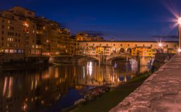 En sikt av Ponten Vecchio i Florence som tas från öst under den blåa timmen precis efter solnedgång arkivbild