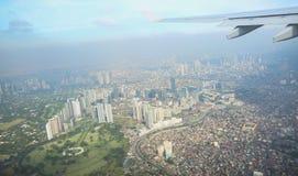 En sikt av staden av Manila till och med fönstret från nivån Imponerat foto av en turist i flykten över huvudstaden royaltyfria bilder