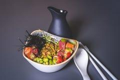 En sikt av en svart tillbringare och en sallad av asiatisk kokkonst i en fyrkantig platta Royaltyfria Foton