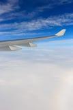 En sikt av vingen av flygplanet från ovannämnda moln för fönster och blå himmel Royaltyfri Foto