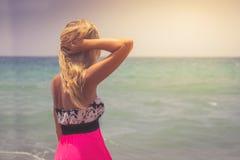 En sikt för tillbaka sida på en underbar ung kvinna som håller ögonen på till havet och lyfter hennes händer på soluppgång royaltyfri bild