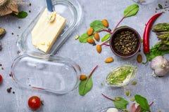 En sikt från ovannämnt på en köksbordsammansättning Nya matställeingredienser mycket av vitaminer på en grå bakgrund Arkivfoto