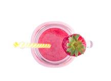 En sikt från ovannämnt på en ny och söt jordgubbesmoothie i en murarekrus som isoleras på en vit bakgrund Organisk och rosa färgd royaltyfria foton