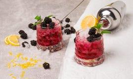 En sikt från ovannämnt på två stora exponeringsglas av kalla drycker med bär och is på grå och vit bakgrund Healthful och Fotografering för Bildbyråer