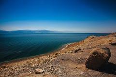 En sikt på en stenig strand, ett hav och avlägsna berg arkivbild