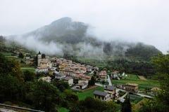 En sikt på en liten italiensk by med moln och dimma fotografering för bildbyråer