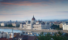 En sikt som förbiser staden av ungersk parlamentbyggnad och Budapest och flodDonauen på den rosa solnedgången, Ungern, Europa Royaltyfri Fotografi