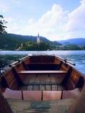 En sikt som kyrktar bak träfartyget på den blödde sjön Arkivbild