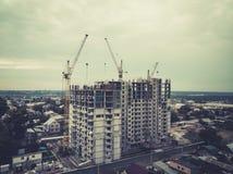 En sikt till den multistorey hyreshusen bland stugor Initial etapp av multifamily husbyggnad i privata sektorn av arkivfoto