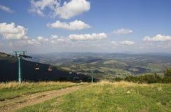 En sikt till den röda öppna cablewaykabinen över överkanten av berget och de buautiful landskapen med blåa berg, gräsplan arkivfoton