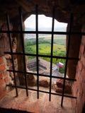 En sikt till och med ett gallerförsett fönster, Lubovna slott Royaltyfri Foto