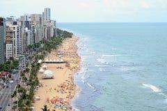 En sikt till stadsstranden med massor av brasilianska människor som uppifrån solbadar och simmar, en sikt av en skyskrapa. Arkivbild