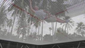 En sikt under trampolinen som en man i kortslutningar och ettkort på den hoppar arkivfilmer