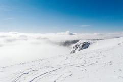 En sikt uppifrån av ett snöig berg till en dal som täckas av en dimma på en solig dag med en klar blå himmel arkivfoto