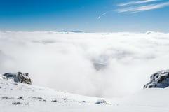 En sikt uppifrån av ett snöig berg till en dal som täckas av en dimma på en solig dag med en klar blå himmel fotografering för bildbyråer