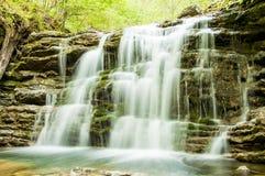 En silkeslen vattenfall i skogen royaltyfria foton