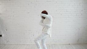 En sinnessjuk svart man i hans forties som bär en tvångströja, dansar och försöker att få ut lager videofilmer