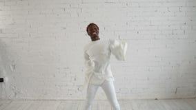 En sinnessjuk svart man i hans forties som bär en tvångströja, dansar och har gyckel stock video
