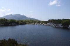 En sjö med en sikt på bergen royaltyfria foton