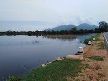en sjö nära vägen och sjön avslutade vid berget royaltyfri fotografi