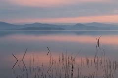 En sjö på skymning, med härliga varma signaler i himlen och vatten Fotografering för Bildbyråer