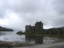 En sjö reflekterar en bild av den Eilean Donan slotten och bron i högländerna av Skottland, Förenade kungariket Arkivbild