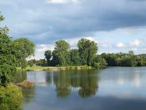En sjö som inramas av grönska Royaltyfri Fotografi