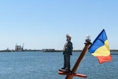 En sjömanleksak och gul och röd romanian flaggan den blått, monterade på en mast för skepp` s Blacket Sea i bakgrunden royaltyfria foton