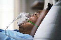 En sjuk asiatisk man i ett sjukhus arkivfoto