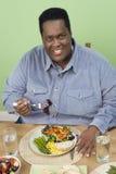 En sjukligt fet man som har mat Fotografering för Bildbyråer