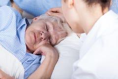 En sjuksköterska hjälper äldre kvinna Arkivfoton