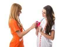 En sjuksköterska lyssnar till den annan sjuksköterskans hjärta Royaltyfria Bilder