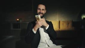 En skäggig affärsman arbetar hemma med bärbara datorn och rymmer en stor bunt av kassa En vuxen man ler Han är lycklig arkivfilmer