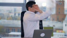 En skäggig affärsman får ilsken på arbete och skrynklar papper stock video