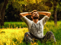 En skäggig man är avslappnande på grönt gräs i parkera Arkivfoton
