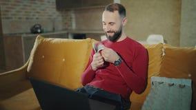 En skäggig man arbetar hemma med bärbara datorn som rymmer en stor bunt av kassa En vuxen man ler Han är lycklig arkivfilmer