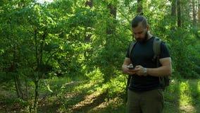 En skäggig man går till och med skogen och söker efter en väg med navigatören GPS lopp stock video