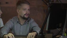 En skäggig man i en skjorta arbetar på datoren och berättar något arkivfilmer