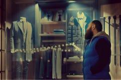 En skäggig man i sporstwearblickar till shoppar fönstret med affärskläder royaltyfri foto