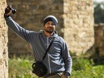 En skäggig man i en stucken hatt står mot väggen i fästningen med en kamera i hans hand och en påse för kameran royaltyfri fotografi