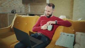 En skäggig man sitter hemma med bärbara datorn och surfar i sociala nätverk för att meddela, att flörta Morgon En vuxen man arkivfilmer