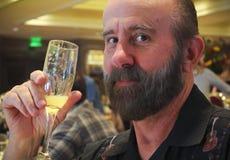 En skäggig man tycker om en mimosa i en restaurang Royaltyfri Fotografi