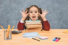 En skämtsam gullig liten flicka har gyckel som litar på tjocka böcker på en grå bakgrund Hennes hår göras in exploaterar arkivfoto