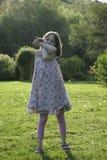 En skämtsam och lycklig ung flicka i en solig trädgård arkivbilder
