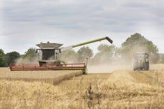 En skördetröska och en traktor royaltyfria foton
